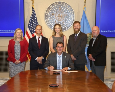 (L-R) Rep. Nicole Miller, Frank Urbanic, Audra Urbanic, Dept. of Corrections Director of Communications and Government Relations Justin Wolf, and Executive Director of Oklahoma Sheriffs' Association Ray McNair join Gov. Kevin Stitt for a ceremonial signing of House Bill 3756.
