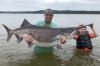 Cody James Watters of Ochelata, with help from son Stetson, 9, holds his rod-and-reel world-record paddlefish that he snagged July 23 at Keystone Lake.