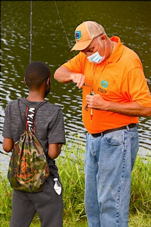 """Wildlife Department Fisheries Biologist Keith Thomas helps a boy in foster care take a sunfish off the hook at the launch event for """"Fostering Outdoor Oklahoma Families"""" at South Lakes Park September 12."""