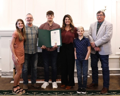 Luke Brooks, third from left, is surrounded by (left to right) his sister, Ava, his father, Rodney, his mother, Juleah, his brother, Zeke and Rep. Rick West at the State Capitol on Monday.