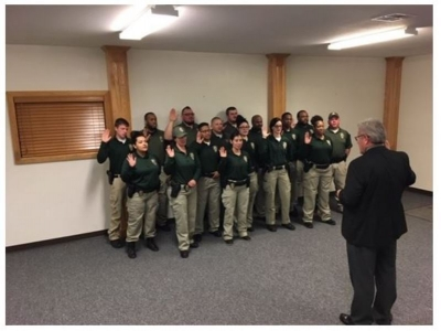 James Rudek, Oklahoma Department of Corrections Director of Director of Community Corrections and Probation and Parole Services, swears in the men and women who graduated recently from an innovative academy that gets more officers on the streets, assisting their colleagues in the field. The new PPOs have a limited commissioning, enabling them to perform more work in the field than their predecessors, until they earn their full law enforcement commission.